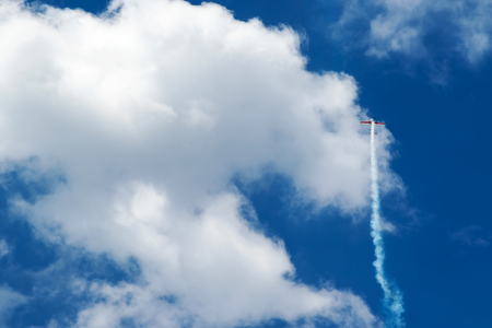 straight up: Small sports plane flies straight up into the blue sky with clouds and releasing smoke