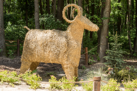 fenced in: Straw decorative ram standing in the woods and fenced rope Stock Photo