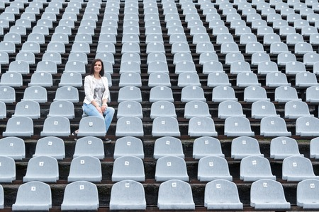 alone person: Lonely beautiful woman sitting on a gray empty stadium tribunes in the rain Stock Photo