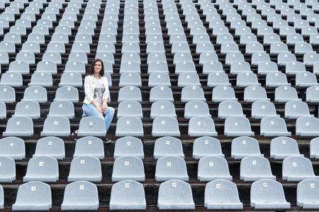 aloneness: Lonely beautiful woman sitting on a gray empty stadium tribunes in the rain Stock Photo
