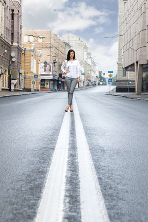 double cross: Portrait of a beautiful business woman on a double lane on the street empty city Stock Photo