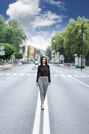 median: Beautiful woman walking on the median strip of the road in the city Stock Photo