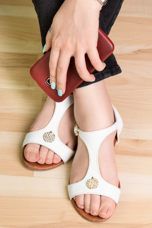 clasp feet: Female hand with a smartphone on the feet in sandals, closeup