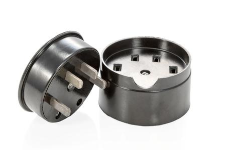 grounded plug: Black ceramic three-phase socket and plug lying beside isolated on white background