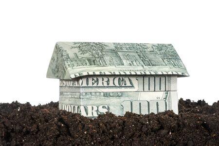 black soil: House origami made from hundred dollar bills standing on black soil isolated on white background
