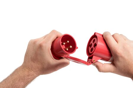 three phase: Mens hold in the hands a three-phase plug and socket red isolated on white background