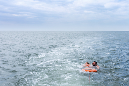 diving save: Man lifeguard with lifebuoy saves child in the sea