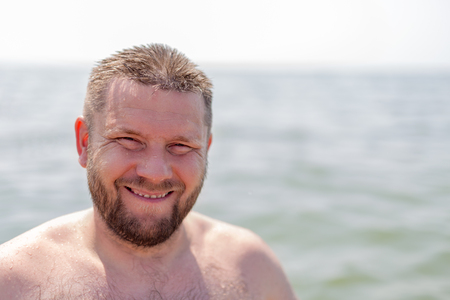 inscrutable: Portrait of a bearded man wet in the sea background