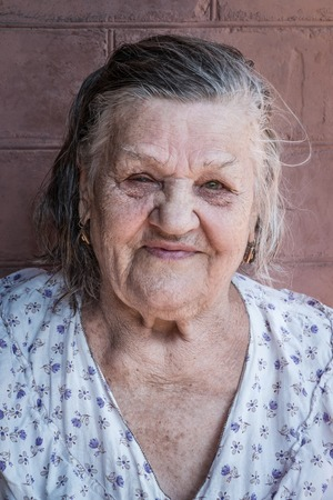 wrinkled brow: Close-up portrait of an old woman in a cotton dress