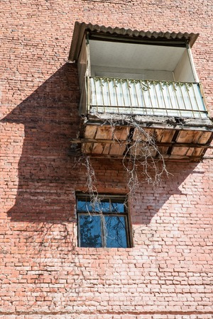 balcony window: Old vintage balcony and below the window on a red brick wall Stock Photo