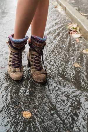 rain wet: Female feet in high boots standing in a puddle in the rain, close-up