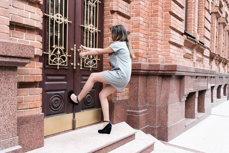Giovane donna in abito corto grigio e scarpe con i tacchi tirando la maniglia della porta d'epoca pendente in gamba