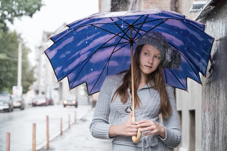 Portrait of a beautiful young woman in a hat under a blue umbrella in the rain on a city street