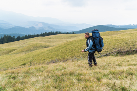 goes: Man tourist with a big backpack goes on the grass against mountains