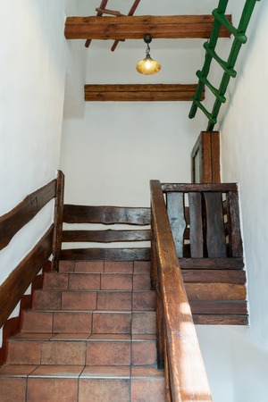 wooden railings: Decorative stairs from floor tiles and wooden railings, with a platform on top