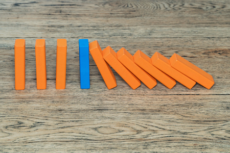 Blue wooden block among the orange stop the domino effect, standing on an old wood table