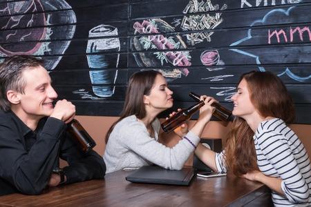 brotherhood: Dos mujeres que se sientan en un café en la mesa de madera, beber cerveza de botellas de vidrio en la hermandad