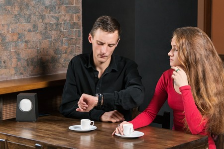 On a date at a cafe for a wooden table and a cup of coffee man exasperated looks at the watch on the hand Standard-Bild