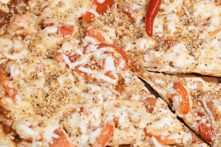 Mexican pizza with chicken, tomatoes, cheese and chili peppers in the middle, closeup. Cut off one piece