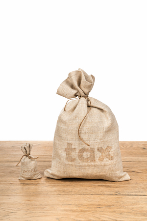 Small bag with the word profit and a big bag of tax lying on wooden table isolated on white background Stock Photo