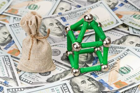 designer bag: Bag with money near the house of designer magnetic on dollars pile Stock Photo