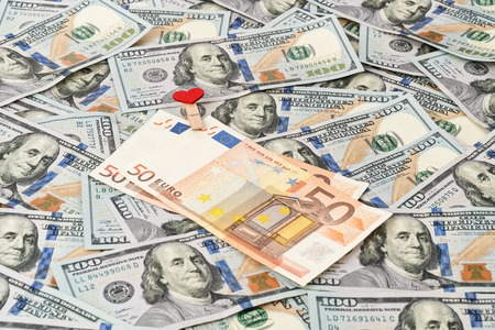 Euro banknotes fastened by a clothespin with a heart lying on a pile of dollars