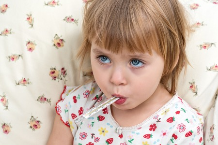 Little blue-eyed child girl with a mercury thermometer in the mouth, closeup