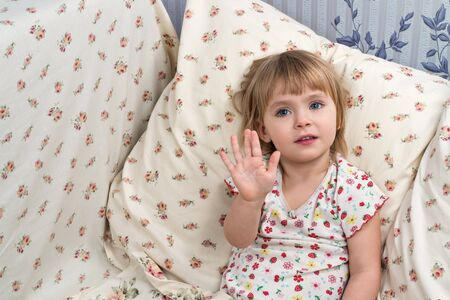 put forward: Portrait of a cute baby girl sitting in the bed, and put forward open palm