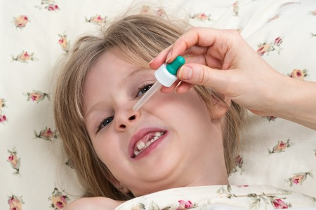 reluctance: Little girl does not want to her nose dripped with a pipette Stock Photo