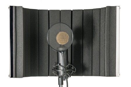 Studio microphone with a shield near the sound-absorbing frame isolated on white background