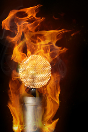 Golden studio microphone stands on the rack and burn a bright flame on black background