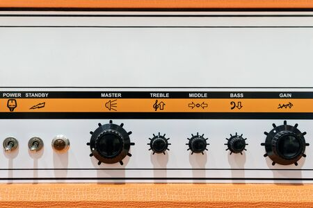 Orange sound control panel with signs, switches, regulators and copyspace