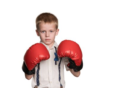 Little serious boy in shirt and red boxing gloves standing in a defensive stance isolated on white background Stock Photo