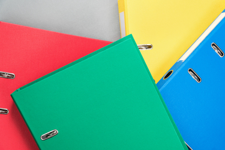 Stationery office multicolored folders randomly stacked on one another, as a background