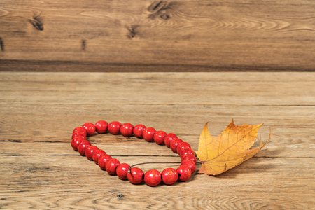 Red wooden beads and dried autumn maple leaf on an old wooden table Stock Photo
