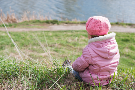 Small child in a pink jacket sits with his back to the camera on the shore, near the water