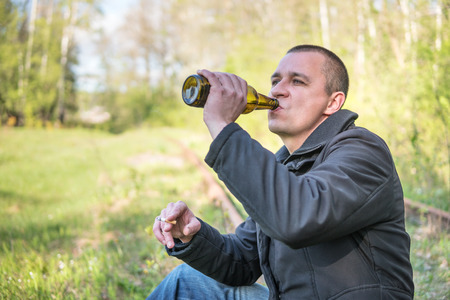 Adult man sitting on rails drinking beer and smoking a cigarette, close-up, with blurred background