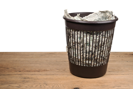 bucket of money: Garbage basket full of crumpled dollars stands on an old wooden table isolated on a white background
