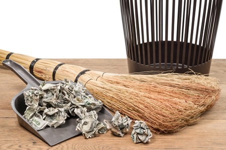 cleaning debt: Crumpled dollars in a garbage shovel next to a broom and a bucket on a wooden surface on a white background Stock Photo