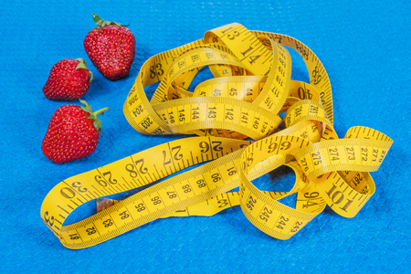 Ripe strawberry with a yellow measuring tape on a blue sports carpet