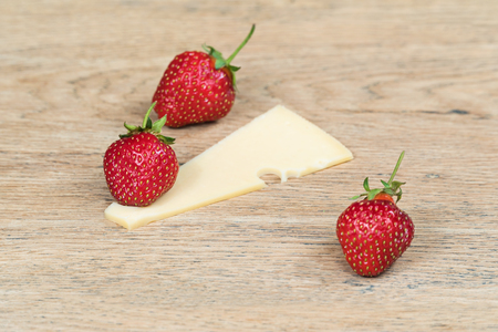 Ripe strawberry and piece of holey cheese on old wooden table