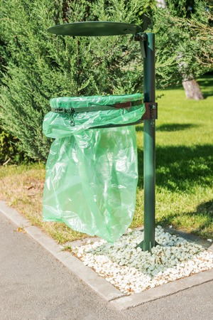 segregate: Trash can with a cellophane bag in a city park by the sidewalk Stock Photo