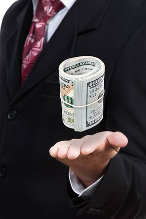 pack of dollars: Businessman in a suit holds an open palm in front of him, above which a bundle of money