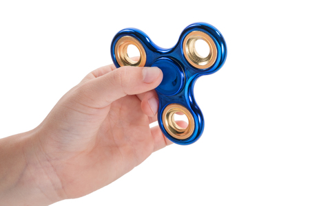 Hands prepared to twist a blue shiny spinner, isolated on a white background