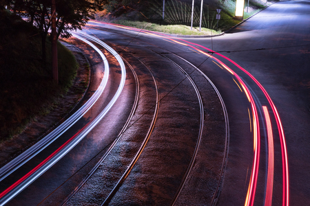 Bend of the road with tram rails in the light of street lamps with a trace from the lights of passing cars Stock Photo