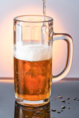 to trickle: Stream of light foam beer is poured into a glass mug