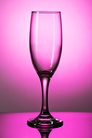 Empty champagne glass on a lumen on a purple background