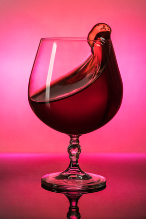 Red wine in a glass splashes out, shot at the light, close-up Stock Photo