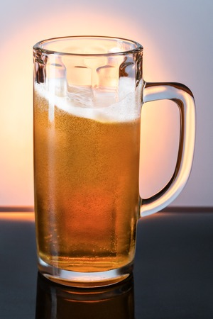 Glass mug with light, frothy beer on the skylight Stock Photo