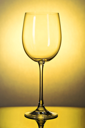 Beautiful empty wine glass toned in yellow, close-up shot against the light Фото со стока